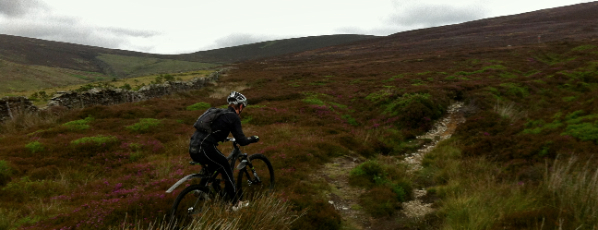 Moorland singletrack climb, clouds drawing in